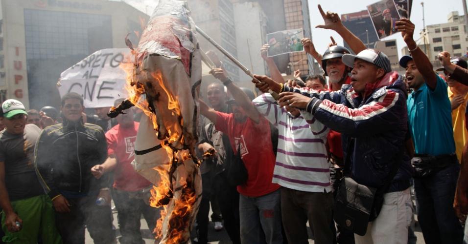 21.mar.2013 - Apoiadores do governo venezuelano e do ex-presidente Hugo Chávez queimam faixa do candidato opositor Henrique Capriles em Caracas. Pelo menos quatro manifestantes ficaram feridos após apoiadores e críticos do governo venezuelano entrarem em confronto