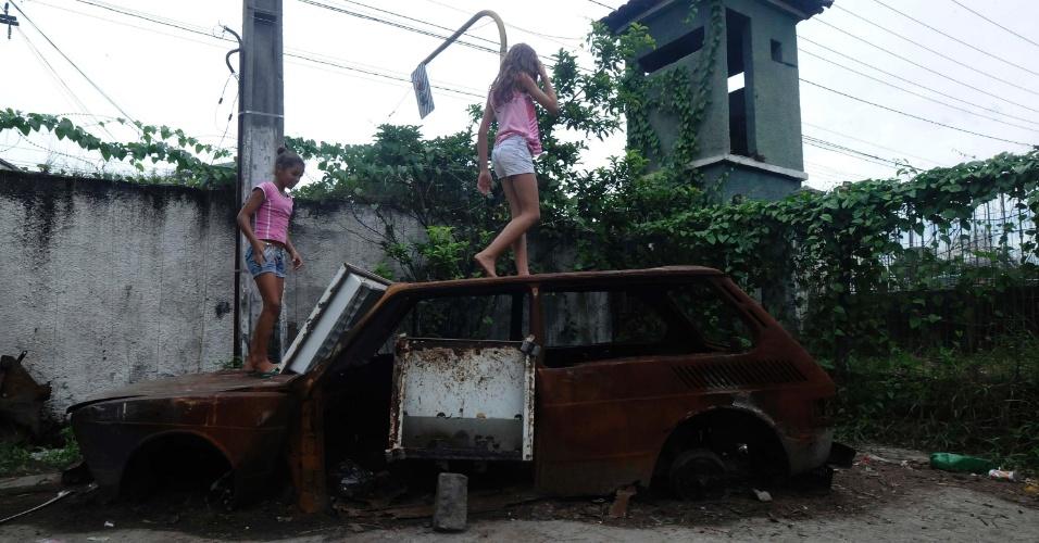 21.mar.2013 - Crianças brincam em carro abandonado no 3º Batalhão de Infantaria, em São Gonçalo (RJ), onde vivem 400 desabrigados do morro do Bumba e demais favelas destruídas com as chuvas de 2010; entulho e lixo juntam água e formam focos do mosquito da dengue no local