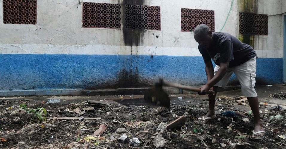 21.mar.2013 - Paulo Mara Martins, 59, vive no 3º Batalhão de Infantaria, em São Gonçalo, junto aos 400 desabrigados do morro do Bumba e demais favelas destruídas com as chuvas de 2010; ele empurra a terra para não obstruir buraco por onde vaza esgoto no local