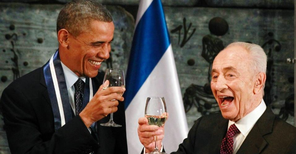21.mar.2013 - Presidente Barack Obama brinda com o Presidente de Israel, Shimon Peres, após Obama ser presenteado com uma Medalha de Distinção Presidencial, durante jantar em Jerusalém