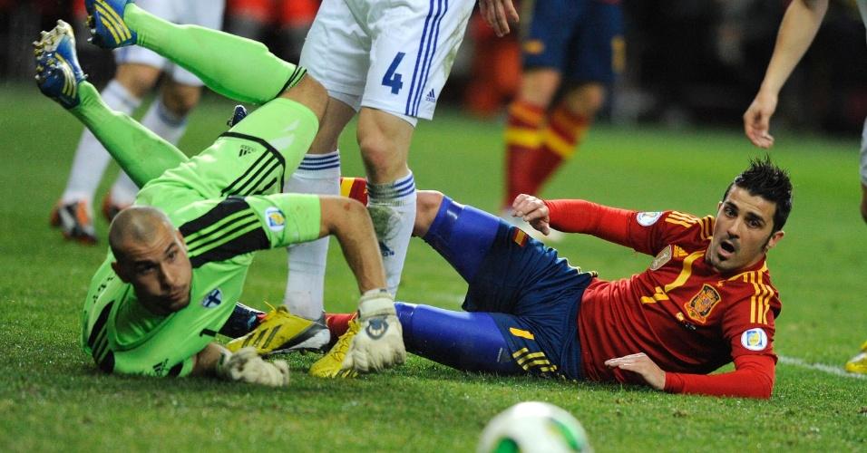 22.mar.2013 - Atacante David Villa (dir), da Espanha, fica caído após encontrão com o goleiro Niki Maenpaa, da Finlândia, durante jogo das eliminatórias da Copa-14; partida terminou empatada por 1 a 1