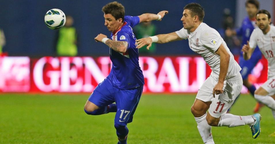22.mar.2013 - Atacante Mario Mandzukic (esq), da Croácia, é marcado por Matija Nastasic, da Sérvia, durante jogo das eliminatórias da Copa-14; croatas venceram por 2 a 0