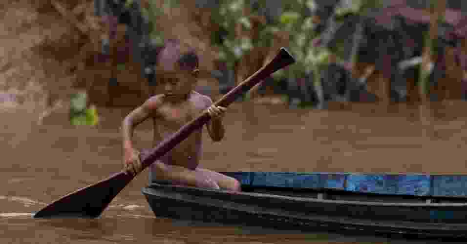 22.mar.2013 - Criança rema no rio Aura, que fica à beira de um lixão, na floresta Amazônica, na véspera do Dia Mundial da Água. O leito do rio está contaminado pelas quase 2.000 toneladas de lixo da cidade de Ananindeua, no Pará. Segundo a ONU, quase metade da população global terá problemas de abastecimento até 2030 - Paulo Santos/Reuters