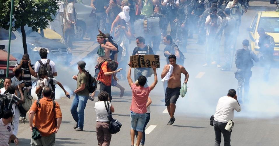 22.mar.2013 - Manifestantes correm após a polícia lançar bombas de gás lacrimogênio durante um protesto contra a reintegração de posse de terreno onde funcionava o antigo Museu do Índio, no Rio de Janeiro. Com tiros e bombas de gás lacrimogênio, a polícia invadiu o lugar para retirar os índios e manifestantes que ocuparam a área, ao lado do estádio do Maracanã, na zona norte da cidade. O governo oferece aos índios do lugar um terreno em Jacarepaguá, na zona oeste do Rio, onde será construída uma aldeia