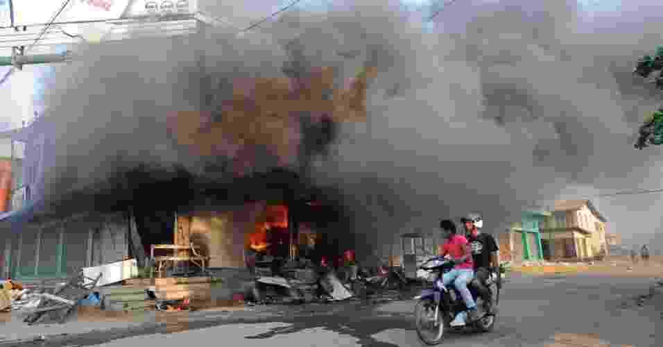 22.mar.2013 - Moradores circulam de moto em frente a edifício em chamas em área de Miktila, região central de Mianmar, onde os confrontos religiosos entre budistas e muçulmanos já deixaram pelo menos 20 mortos - Soe Than Win/AFP
