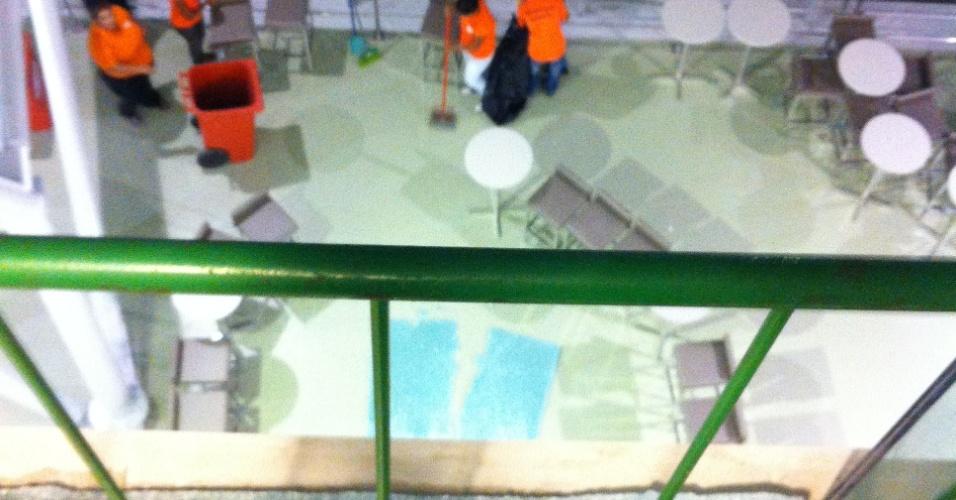 Funcionários recolhem cacos de vidraça que caiu de uma altura de 10 metros no Castelão, em Fortaleza