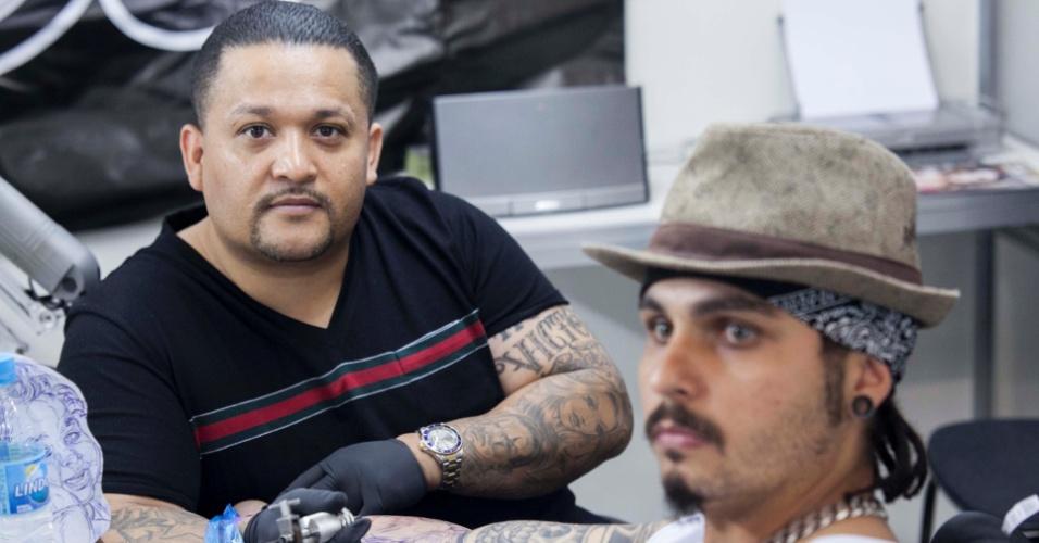 23.mar.2013 - O tatuador mexicano Jose Lopez (à esq.) mostra seu trabalho durante a 8ª edição da São Paulo Tattoo Festival, convenção de tatuagem que reúne artistas e admiradores no centro de São Paulo, neste sábado (23) e domingo (24)