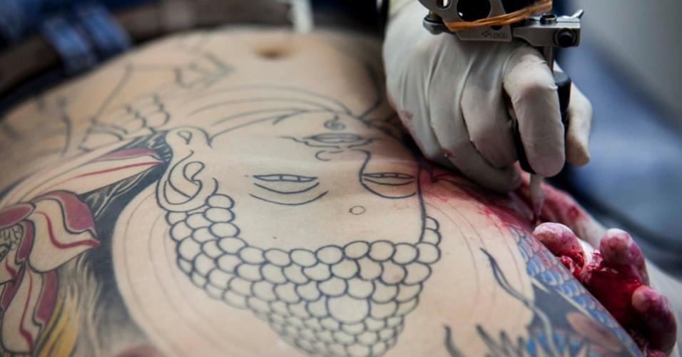 23.mar.2013 - Tatuador trabalha durante a 8ª edição da São Paulo Tattoo Festival, convenção de tatuagem que reúne artistas e admiradores no centro de São Paulo, neste sábado (23) e domingo (24)