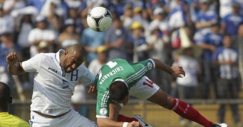 23.mar.2013 - Victor Bernardez (branco) e Javier 'Chicharito' Hernández (verde) disputam bola na partida entre Honduras e México pelas eliminatórias da Copa-14; jogo terminou 2 a 2