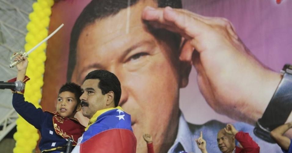 25.mar.2013 - Presidente da Venezuela, Nicolás Maduro (esquerda), segura criança vestida como o líder político Simón Bolívar, tendo ao fundo um pôster do ex-presidente Hugo Chávez, em comício no Estado de Lara