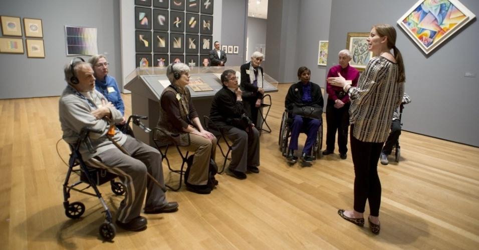"""26.mar.2013 - Grupo com vários níveis de deficiência visual realiza visita guiada à mostra """"Inventando Abstração"""" ao Museu de Arte Moderna de Nova York, o MoMa. Embora o lugar atraia visitantes de várias partes do mundo para ver suas obras, todos os meses o grupo vai ao museu para conhecer as obras expostas, com o auxílio de uma guia especial (direita, de pé)"""
