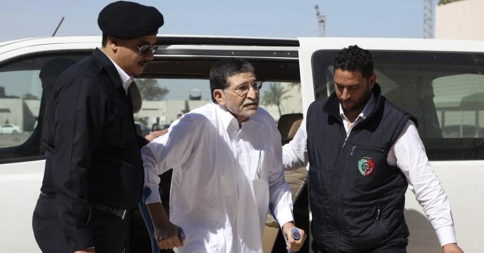 26.mar.2013 - Homens ajudam o ex-chefe do serviço de inteligência externa do ditador Muammar Gaddafi, Bouzid Dorda (centro, de branco), a descer de seu veículo, na porta de tribunal em Trípoli, na Líbia