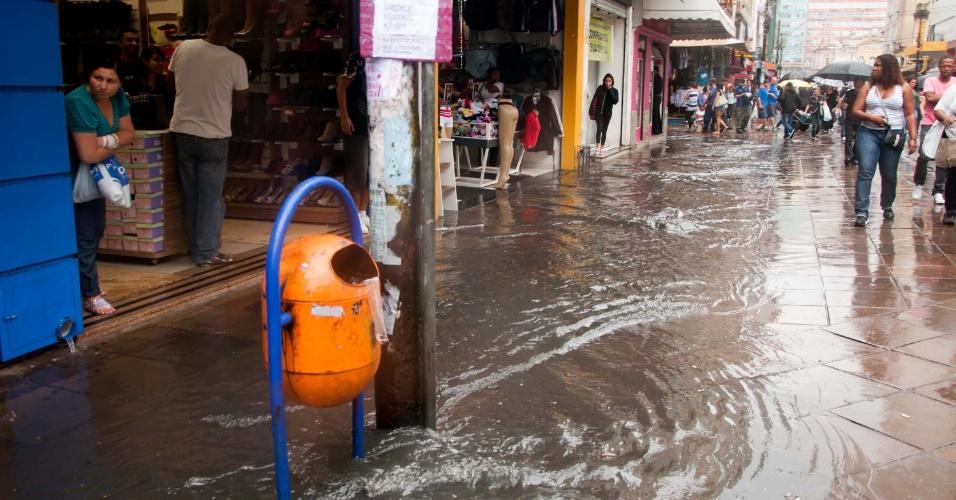 26.mar.2013 - Lojistas enfrentam chuva e alagamento na rua Voluntários da Pátria, em Porto Alegre (RS), nesta terça-feira. Hoje é comemorado o aniversário da cidade