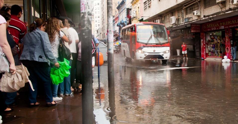 26.mar.2013 - No início da tarde desta terça-feira, pedestre enfrenta chuva na rua Voluntários da Pátria, em Porto Alegre (RS). Hoje é comemorado o aniversário da cidade