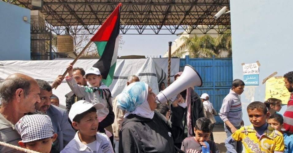 26.mar.2013 - Palestinos do campo de refugiados sírios de Al Yarmuk, ao sul de Damasco, protestam em frente à sede da Agência da ONU para Refugiados Palestinos, em Beirute, capital do Líbano
