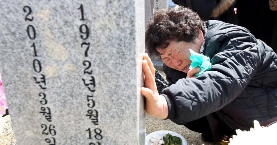 26.mar.2013 - Parente de vítima do afundamento do navio de guerra sul-coreano Cheonan chora diante de sua tumba, no 3º aniversário da tragédia, no Cemitério Nacional de Daejeon, em Seul, capital da Coreia do Sul