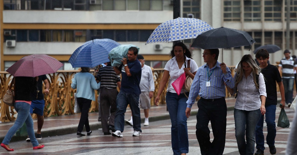 26.mar.2013 - Pedestres se protegem da chuva na tarde desta terça-feira (26) no viaduto Santa Efigênia, no Centro de São Paulo (SP)