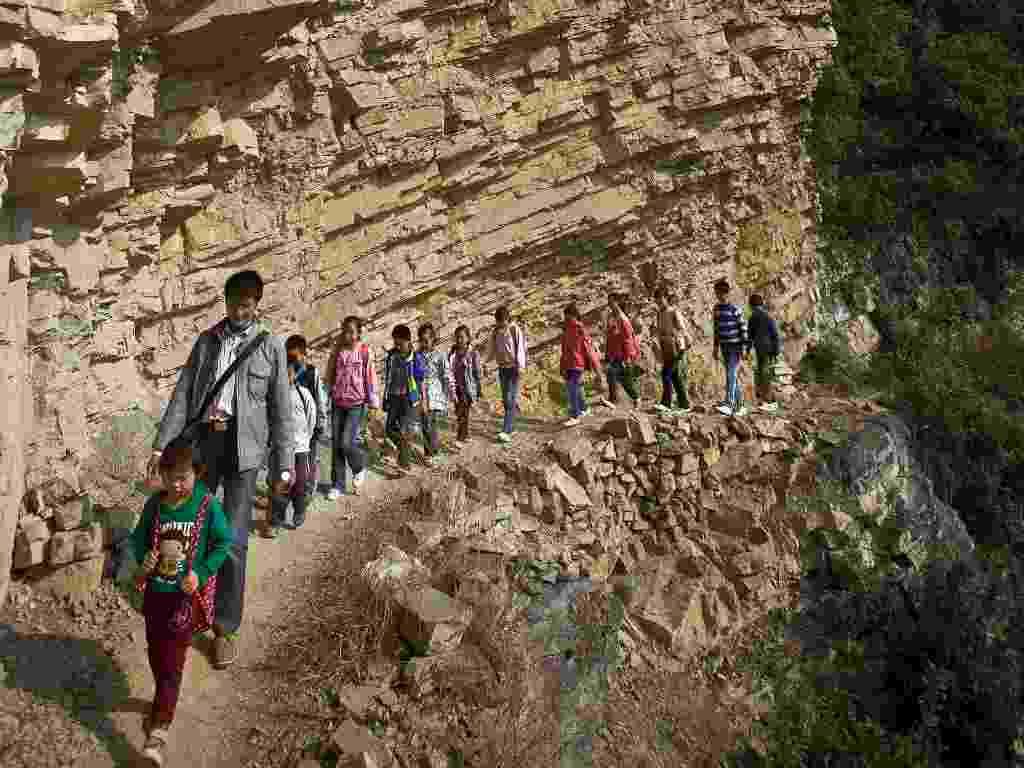 Na China, crianças têm de atravessar caminho às margens de precipício para ir à escola primária de Banpo em Shengji - Stringer/China