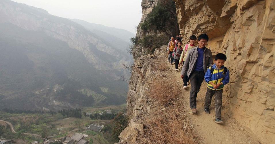 No caminho, as crianças são acompanhadas pelo diretor e professor de matemática Xu Liangfan, 37. O caminho  foi esculpido em penhascos há mais de 40 anos e é o único caminho entre a vila Gengguan e da escola, de acordo com a mídia local