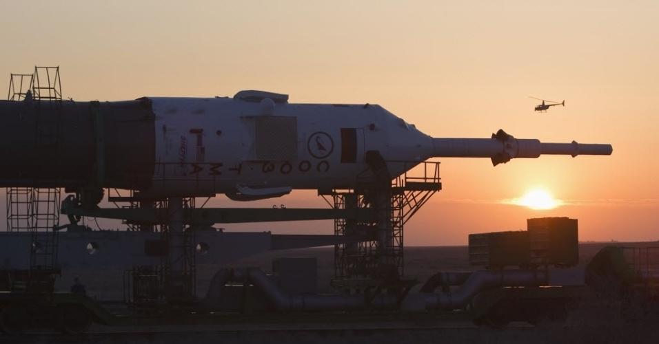 26.mar.2013 - Helicóptero faz segurança da nave russa Soyuz TMA-08M, durante seu transporte de trem para a plataforma de lançamento do cosmódromo de Baikonur, no Cazaquistão