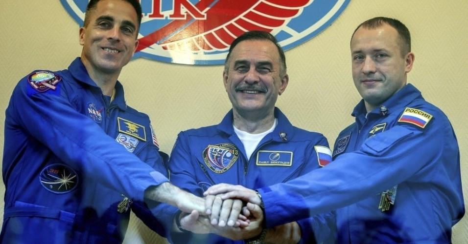 27.mar.2013 - O mecânico de voo Chris Cassidy (à esquerda), astronauta da Nasa (Agência Espacial Norte-Americana); o cosmonauta russo Pavel Vinogradov (centro), comandante da nave Soyuz; e o cosmonauta russo Alexander Misurkin (à direita) posam para os fotógrafos, na véspera de serem enviados ao espaço. O trio vai integrar a missão 35 da Estação Espacial Internacional (ISS, na sigla em inglês)