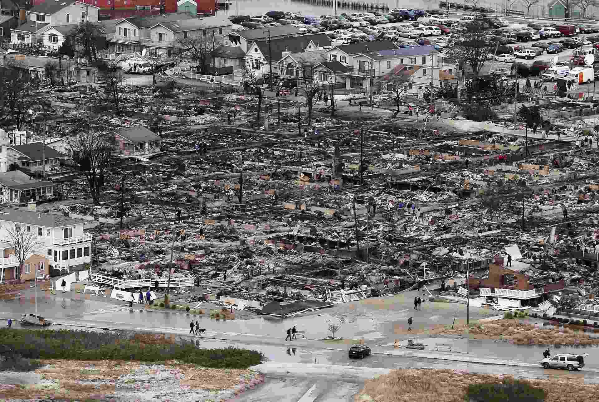 27.mar.2013 - Vista aérea mostra devastação causada pela supertempestade Sandy em área residencial do Queens, bairro de Nova York, na costa leste dos Estados Unidos, em outubro de 2012. As catástrofes naturais e as provocadas pelo homem custaram US$ 186 bilhões ao mundo em 2012 (cerca de R$ 376,5 bilhões), o terceiro maior prejuízo da história, segundo estudo da Swiss Re. A passagem do furacão Sandy foi a que mais causou prejuízo no ano passado, somando as perdas no país, de US$ 70 bilhões (cerca de R$ 141 bilhões), e os custo pagos pelas seguradoras, de US$ 35 bilhões (aproximadamente R$ 70,5 bilhões) - os Estados Unidos registraram nove dos dez incidentes mais caros do ano, somando US$ 65 bilhões (R$ 131 bilhões) em perdas seguradas - Mario Tama/Getty Images/AFP