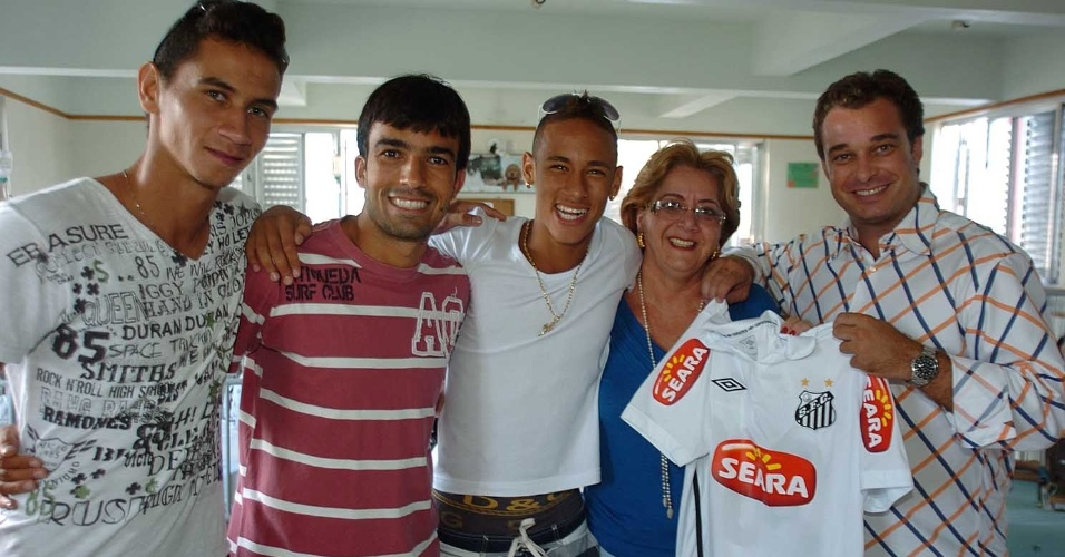 Ganso, Roberto Brum, Neymar e Jamelli oferecem uniforme do Santos a representante de Lar Espírita que cuida de crianças em Santos (03/2010)