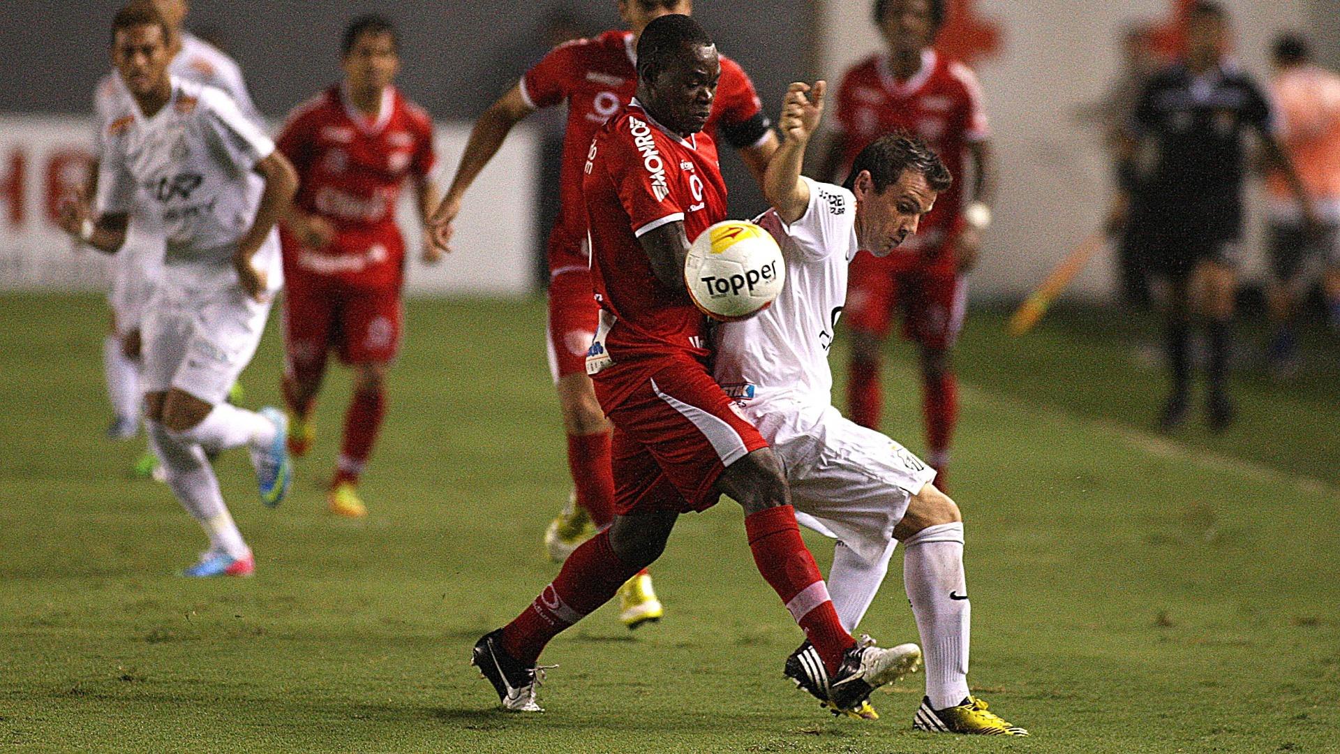 28.mar.2013 - O meia Montillo tenta desviar da marcação durante a partida entre Santos e Mogi Mirim válida pelo Campeonato Paulista, na Vila Belmiro
