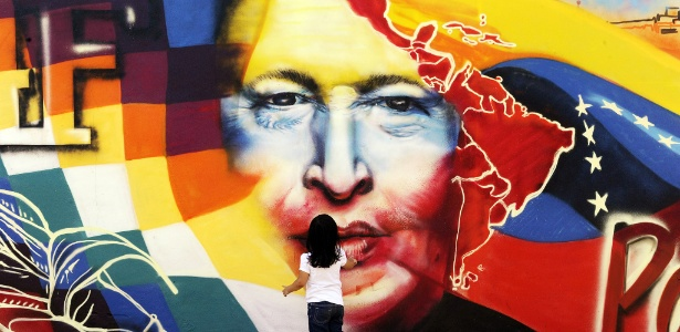 Garota observa grafite com a figura do presidente Hugo Chávez, perto do Quartel da Montanha, na Venezuela - Juan Barreto/AFP