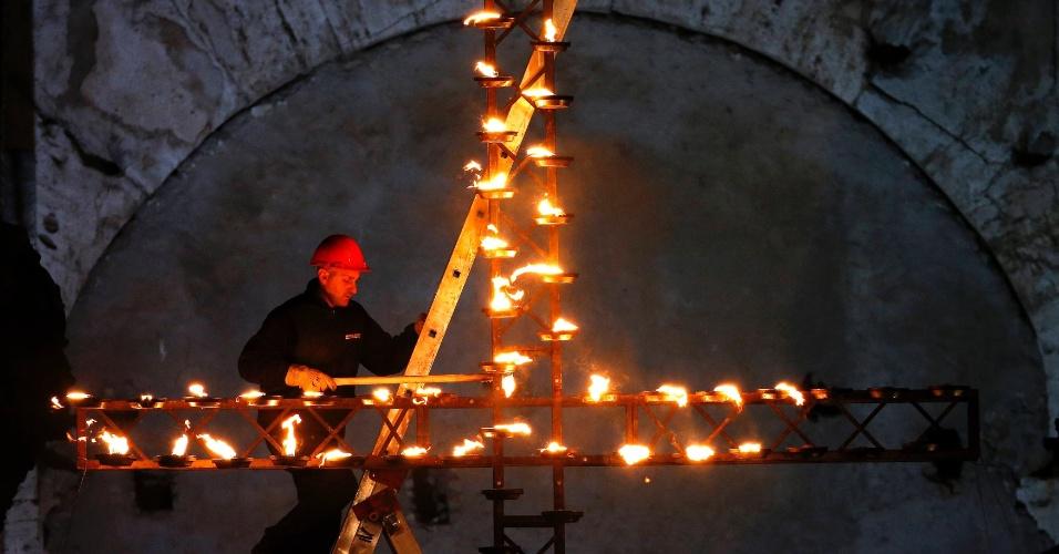 29.mar.2013 - Homem acende cruz antes do papa Francisco dar início a via-sacra durante as celebrações da Sexta-Feira Santa, em frente ao Coliseu de Roma