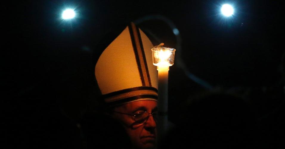 30.mar.2013 - 30.mar.2013 - Papa Francisco carrega vela durante a vigília pascal neste sábado na Basílica de São Pedro, no Vaticano. A vigília de Páscoa é a primeira celebração da ressurreição de Jesus