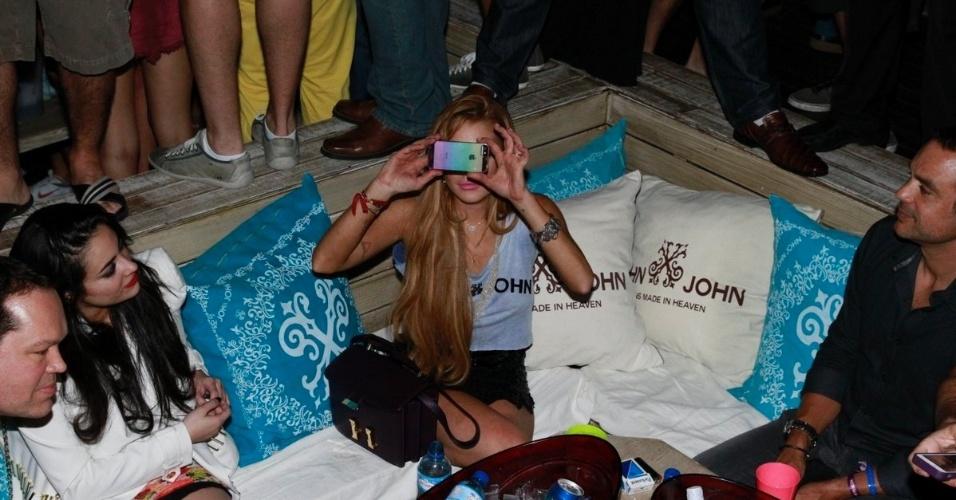 30.mar.2013 - Lindsay Lohan tira fotos em balada em Florianópolis. A atriz está no Brasil para participar de festa de uma marca de roupas