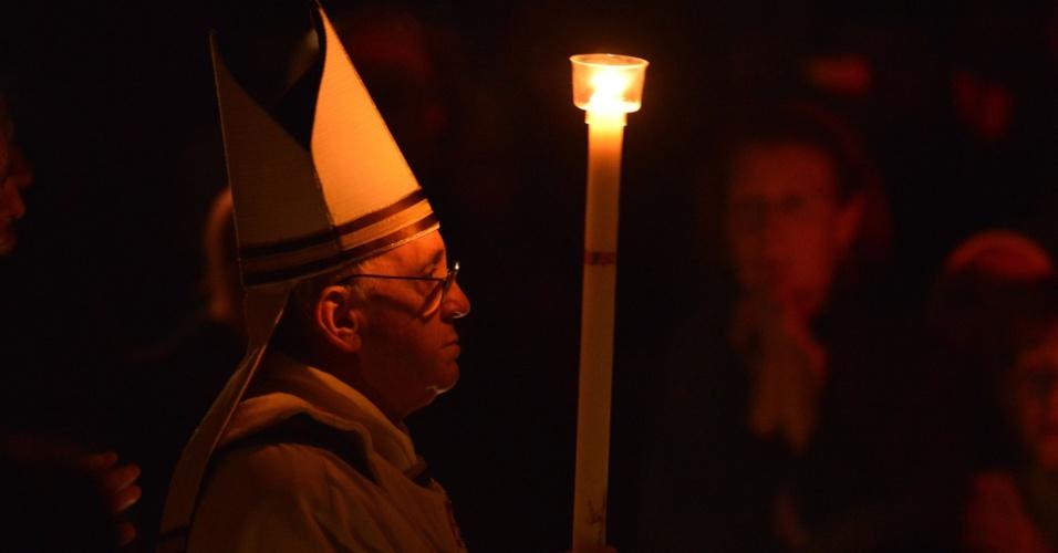 30.mar.2013 - Papa Francisco carrega vela durante a vigília pascal neste sábado na Basílica de São Pedro, no Vaticano. A vigília de Páscoa é a primeira celebração da ressurreição de Jesus