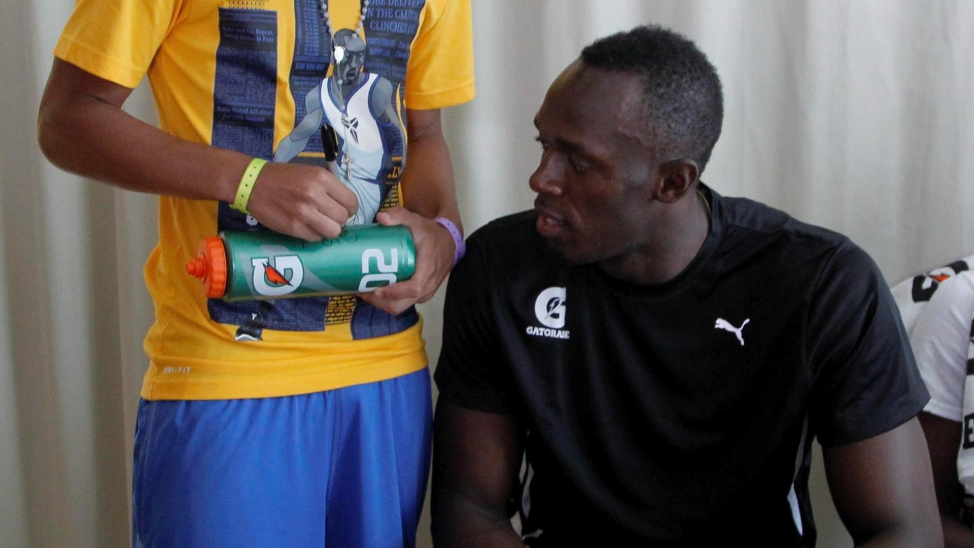 30.mar.2013 - Usain Bolt ganha autógrafo de Gabigol, jogador da base do Santos, depois de jogarem juntos futevôlei em Copacabana:
