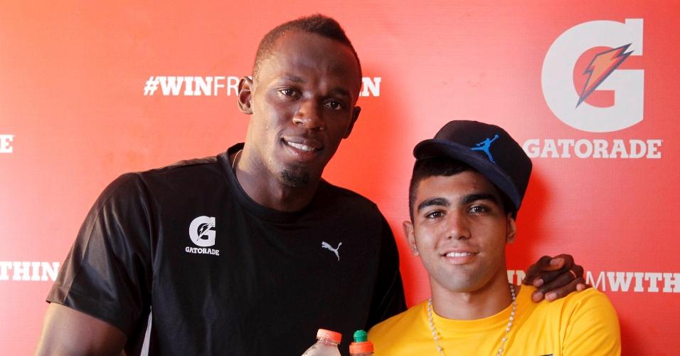 30.mar.2013 - Usain Bolt posa ao lado de Gabigol depois de jogarem futevôlei em Copacabana, onde o jamaicano disputa prova de 150 m no próximo domingo