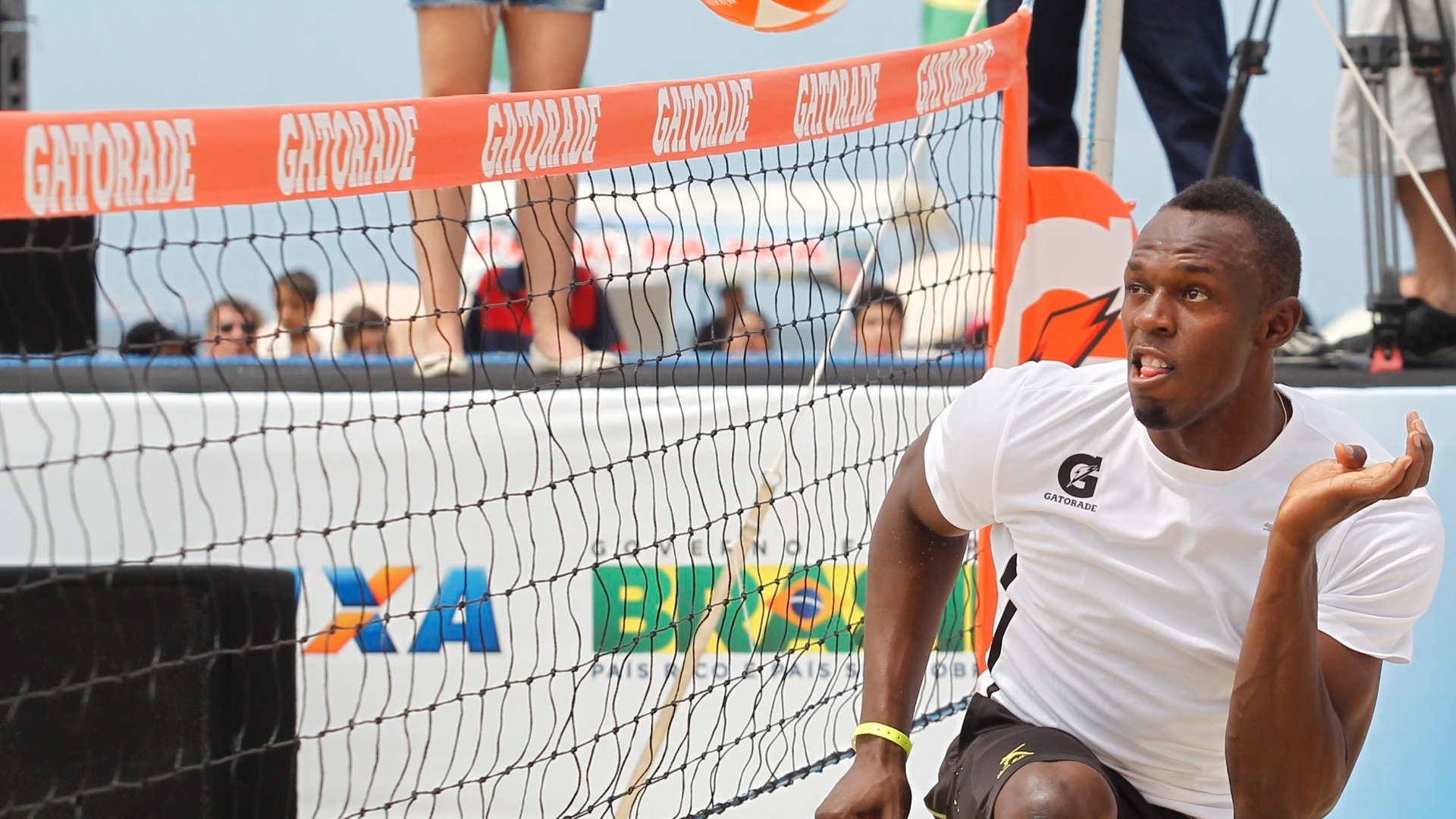 30.mar.2013 - Usain Bolt salta para cabecear bola durante partida de futevôlei em Copacabana, no Rio de Janeiro