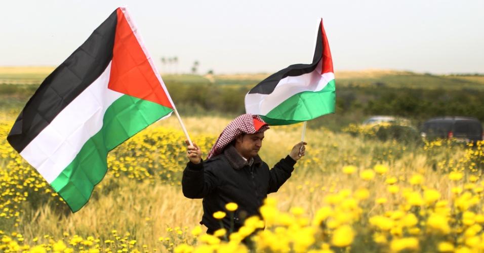 31.mar.2013 - Homem segura bandeiras da Palestina ao passar por um campo de flores durante manifestação pelo Dia da Terra, na faixa de Gaza, neste domingo (31). A data marca a morte de seis manifestantes por policiais israelenses em 1976 durante um protesto contra o confisco de terras árabes na Galileia