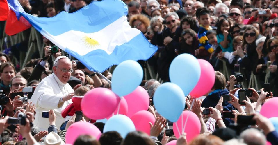 31.mar.2013 - O papa Francisco acena para fiéis próximo a uma bandeira da Argentina, na praça São Pedro, após a celebração da missa de Páscoa, este domingo (31), no Vaticano