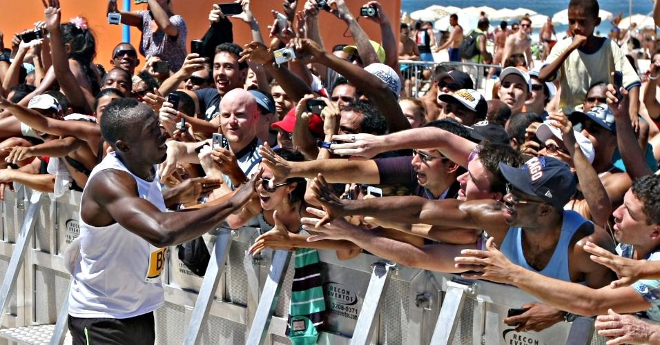 31.mar.2013 - Usain Bolt interage com os fãs após vencer desafio na praia de Copacabana