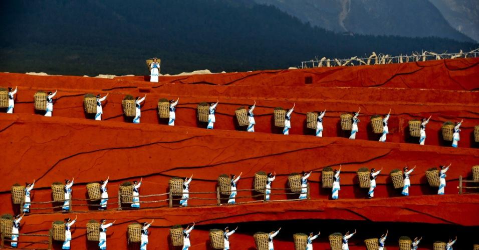 1º.abr.2013 - Atores e dançarinos chineses atuam na produção cênica em maior altitude do mundo, realizada a 3.300 metros acima do nível do mar, aos pés da montanha Jade Dragon, em Lijiang, no sul da China. A performance, feita por membros de etnias minoritárias da região, foi produzida pelo diretor de cinema Zhang Yimou