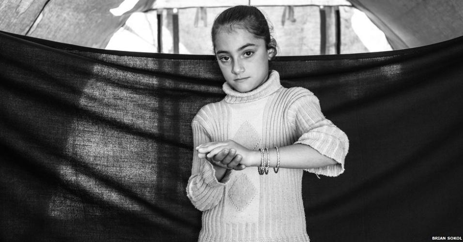 1º.abr.2013 - Cerca de um milhão de sírios abandonaram suas casas desde que a guerra civil explodiu no país, há dois anos. Segundo a ONU, cerca de 400 mil sírios cruzaram fronteiras em busca de abrigo em campos de refugiados na Turquia, no Iraque e no Líbano. May, com apenas oito anos, mostra os braceletes, a coisa mais valiosa que conseguiu carregar. Ela conta, no entanto, que sente saudades da boneca Nancy, no campo de Domiz.