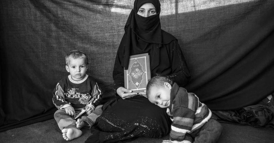 1º.abr.2013 - Cerca de um milhão de sírios abandonaram suas casas desde que a guerra civil explodiu no país, há dois anos. Segundo a ONU, cerca de 400 mil sírios cruzaram fronteiras em busca de abrigo em campos de refugiados na Turquia, no Iraque e no Líbano. Iman, 25 anos, carregou apenas seu filho Ahmed, sua filha Aisha e o Corão ao fugir de casa em Aleppo. No campo de Nizip, em território turco, ela conta que o livro sagrado dos muçulmanos lhe oferece proteção
