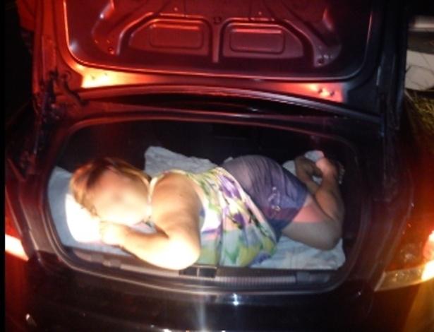 1°.abr.2013 - Em imagem divulgada nesta segunda-feira (1º), a Polícia Rodoviária Federal flagra uma mulher dormindo no porta-malas de um veículo Vectra, com placa de São Paulo, em Guaíra, no Oeste do Paraná. O episódio aconteceu na segunda-feira passada (25), segundo a PRF. A mulher era mãe do motoristao do carro, que levava mais três pessoas, incluindo o condutor. A PRF diz que eles viajavam pela BR-272 rumo ao Paraguai, onde iriam fazer compras para a Páscoa. O motorista foi autuado por transporte de pessoa no compartimento de carga, infração considerada gravíssima, perdendo sete pontos na carteira e tendo que pagar multa no valor de R$ 191,54. A mulher passou para dentro do carro, que seguiu viagem