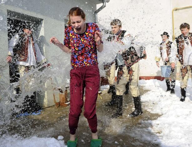 1°.abr.2013 - Jovens eslovacos vestidos em trajes tradicionais jogam balde de água fria sobre mulher durante celebrações da Páscoa na aldeia de Trencianska Tepla (145 km ao norte de Bratislava), nesta segunda-feira (1°). Segundo a tradição do país, o banho de água dado por homens nas mulheres no início da primavera evoca força, juventude e beleza