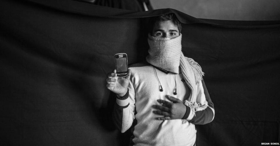 """1º.abr.2013 - O fotógrafo Brian Sokol, que vive na Índia, percorreu alguns dos campos de refugiados sírios. Com ajuda da Acnur (Agência da ONU para Refugiados), ele retratou alguns refugiados junto aos poucos pertences que os acompanharam. O fotógrafo também visitou a região do Vale do Beká, no Líbano, onde encontrou Yusuf, de Damasco. Ele mostra o celular. """"Com isso posso ligar para meu pai"""", diz. Ele também pode ver fotos da família."""
