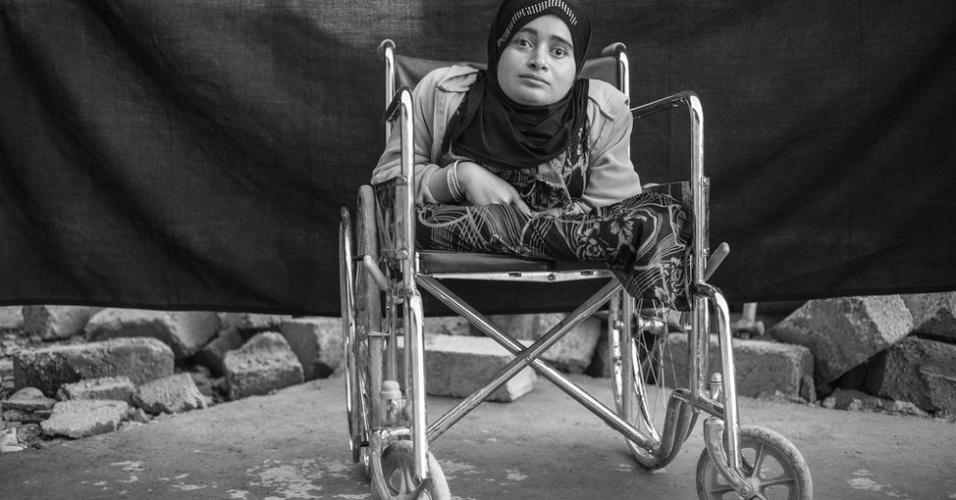 """1º.abr.2013 - O fotógrafo Brian Sokol, que vive na Índia, percorreu alguns dos campos de refugiados sírios. Com ajuda da Acnur (Agência da ONU para Refugiados), ele retratou alguns refugiados junto aos poucos pertences que os acompanharam. Alia, de 24 anos, é cega e deficiente física. Ela deixou sua casa em Daraa e conta que a única coisa que trouxe ao campo de Domiz, no Curdistão iraquiano, foi sua """"alma"""". A cadeira de rodas ela não conta, já que considera uma extensão do corpo."""