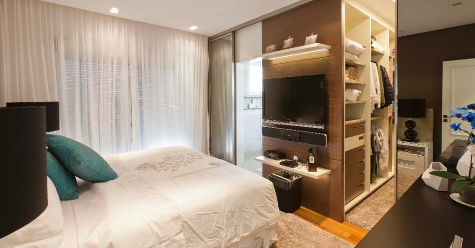 Integrado ao dormitório pela porta de correr espelhada e o piso de madeira, o closet (5 m²) assinado pela arquiteta Mayra Lopes tem sistema modulado, da Ornare, em MDF com acabamento laminado e ferragens da Blum