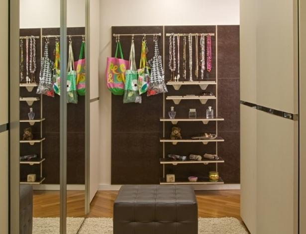 Para acomodar os acessórios, Samy e Rick Dayan criaram o painel revestido em couro, com prateleiras em pau ferro e MDF branco. Repare na iluminação mista que permite a visualização das peças