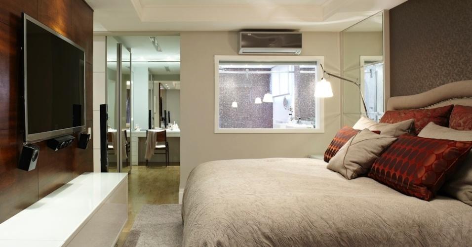 Projetado segundo o desenho da arquiteta Selma de Sá, este closet com mobiliário em MDF integra-se ao dormitório pelo piso de madeira e através da porta de correr