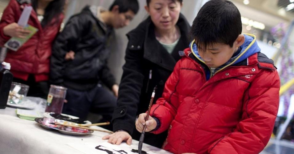 2.abr.2013 - Criança autista pinta em cerimônia realizada para ajudar pessoas com o transtorno que vivem em áreas rurais da China